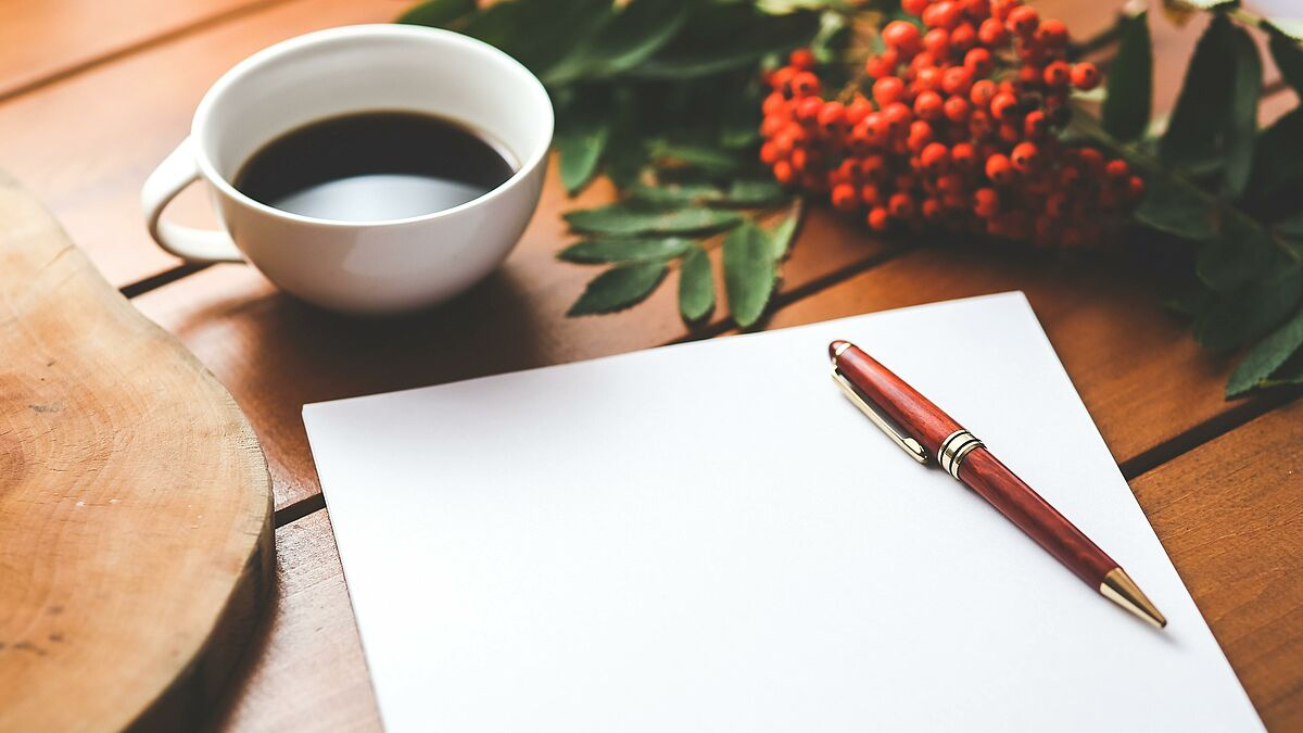 blank paper with pen and coffee cup on wood table @pexels.com